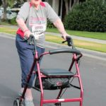 A senior citizen racing with her support device