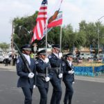 An image of cadets marching with USA flags