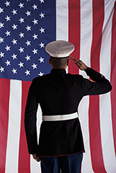 An image of a Man in U.s. Marine Corps Uniform Saluting American Flag